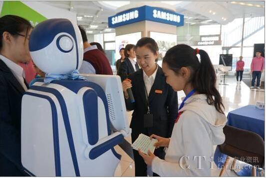 (西单电信营业厅的工作人员正与客户一起跟智能机器人交流)